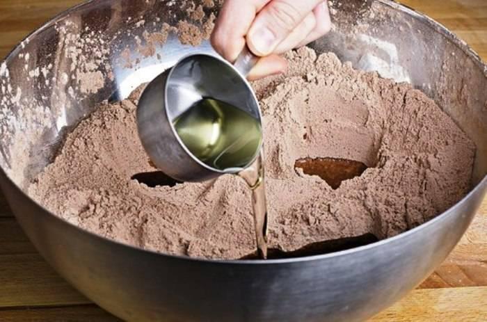 Затем сделайте в смеси три углубления, в которые влейте отдельно экстракт ванили, яблочный уксус и  масло.