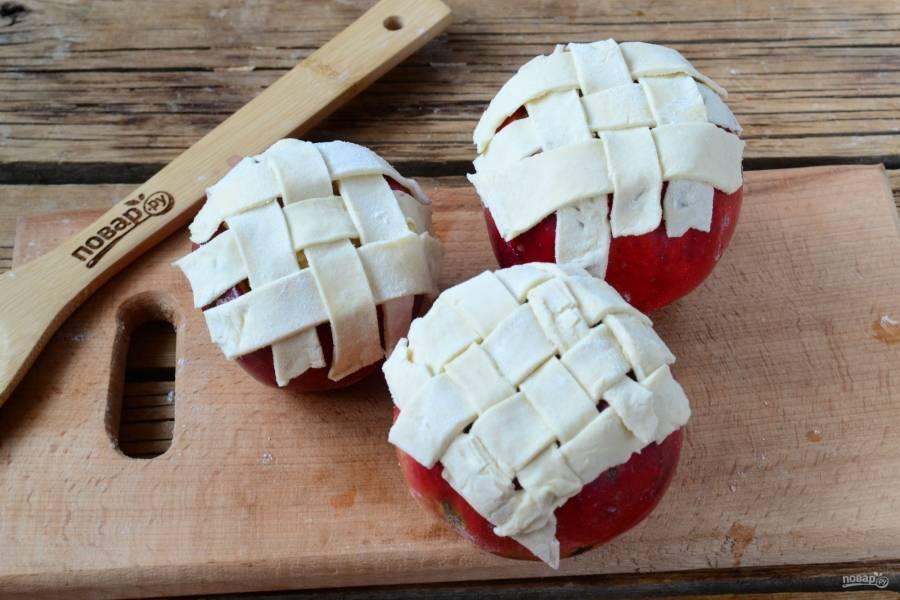 Тесто, которое вы предварительно разморозили и раскатали, порежьте на полоски шириной 8 мм. Из этих полосок сделайте сеточку на яблоках.