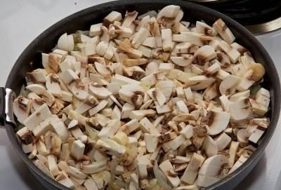 Сразу же после этого выкладываем в емкость с жареным луком измельченные грибы, и все хорошо перемешав деревянной лопаткой, жарим ингредиенты еще в течение 10-15 минут до тех пор, пока не испарится весь грибной сок, а шампиньоны не приобретут коричневатый цвет. Внимание: не забываем продолжать время от времени помешивать все лопаткой. После этого выключаем конфорку и оставляем овощную зажарку в стороне, чтобы она немного остыла.