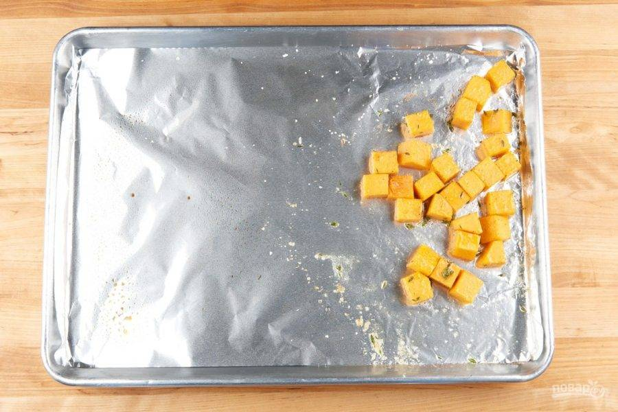 2. Кабачок нарежьте небольшими кубиками. Выложите овощ на противень с фольгой. Немного посыпьте тимьяном, солью, перцем и добавьте 2 ч. ложки масла. Запекайте кабачок при 200 градусах в течение 10 минут в духовке.