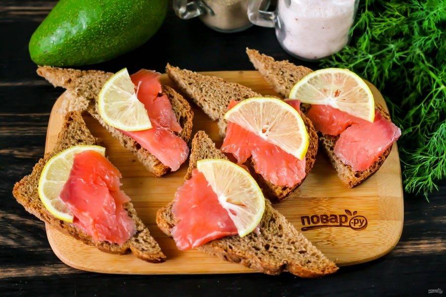 Выложите на них нарезку красной рыбы и ломтики лимона. По желанию можно смазать хлеб сначала майонезом, но красная рыба и авокадо сами по себе жирные, поэтому от соуса лучше отказаться.