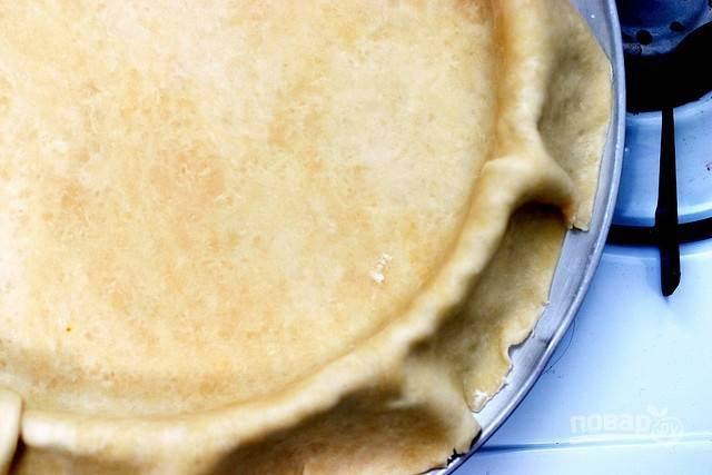 После этого раскатайте тесто в диск в 6 мм толщиной. Выложите его в круглую форму смазанную маслом, чтобы края висели по бокам.