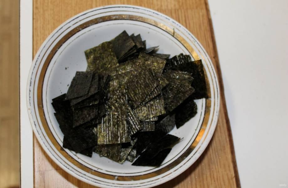 2.Листы нори нарезаю небольшими квадратикам (удобнее это делать ножницами) и складываю их в тарелку.