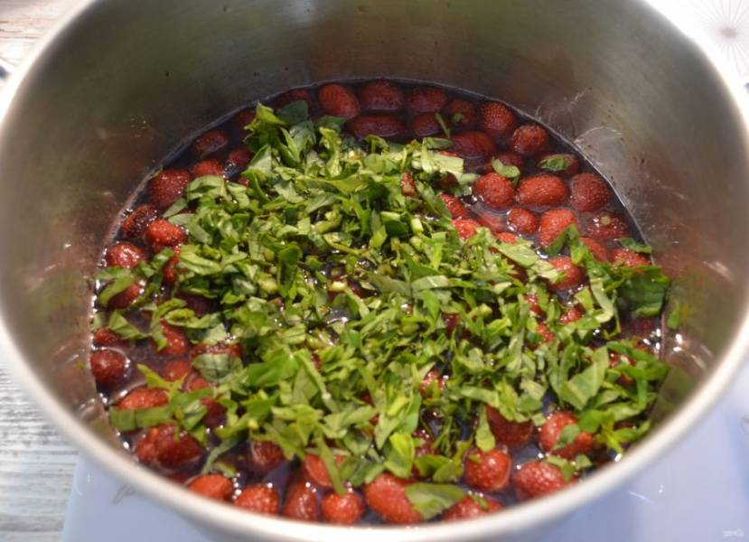 Снова нагрейте варенье до закипания, мелко нарежьте базилик, добавьте к ягодам.