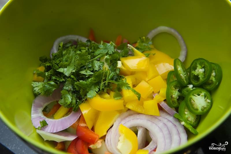 6. В большой салатнице смешайте нарезанные овощи и зелень - огурец, болгарский перец, лук, горький перец и кориандр.
