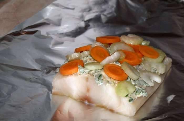 Раскладываем филе палтуса на фольгу (каждое филе - на отдельную фольгу). Сначала намазываем рыбу смесью из сливочного масла, сверху кладем овощи.