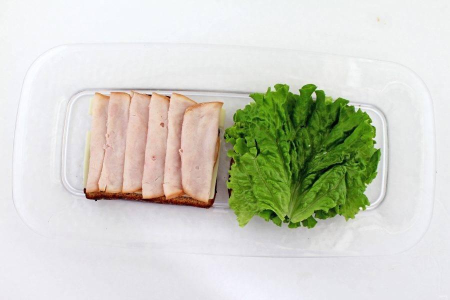 Затем на майонез положите лист салата, а на сыр — ветчину, порезанную тонкими ломтиками.