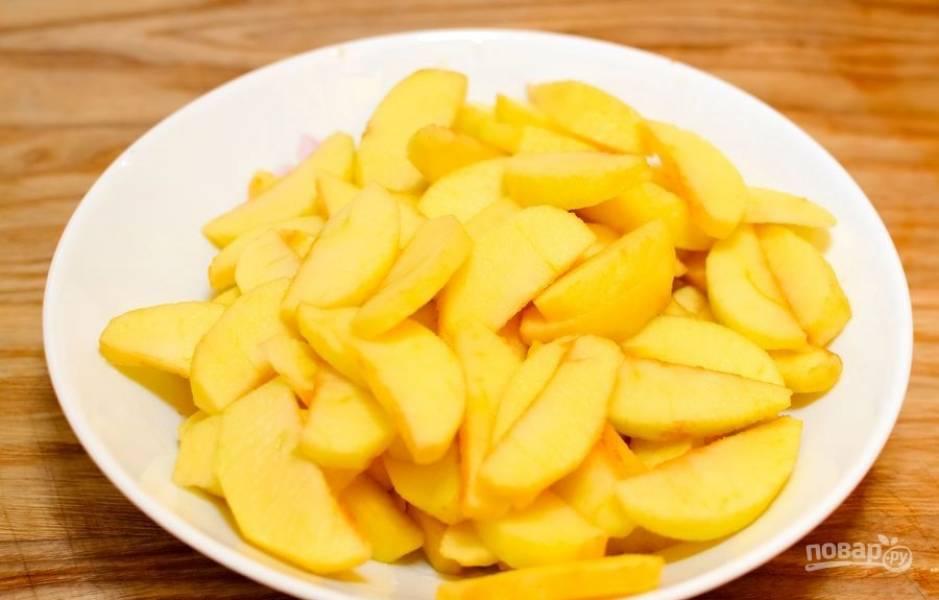 Нарежьте яблоки дольками и сбрызните их соком половины лимона.