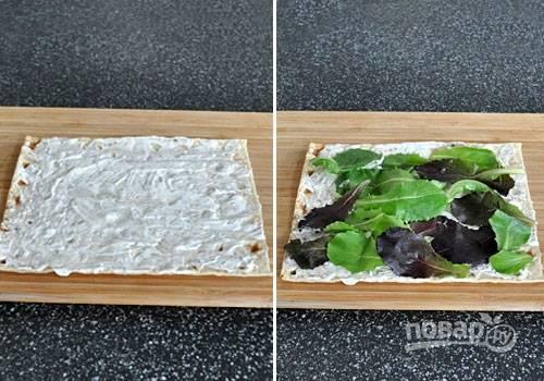 1. Выложите лист салата на стол, смажьте его небольшим количеством майонеза. Также рекомендую попробовать использовать чесночок, будет очень пикантный вкус у рулетиков. Сверху распределите листья салата и другую зелень.