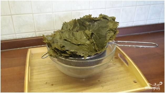 1.Перед тем как приготовить долму из баранины, займитесь подготовкой виноградных листьев. Для начала залейте их кипятком и дайте пропариться 5 минут.