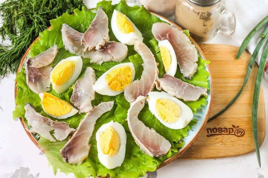 Нарежьте кусочки рыбы слайсами и выложите ее между яичных ломтиков.