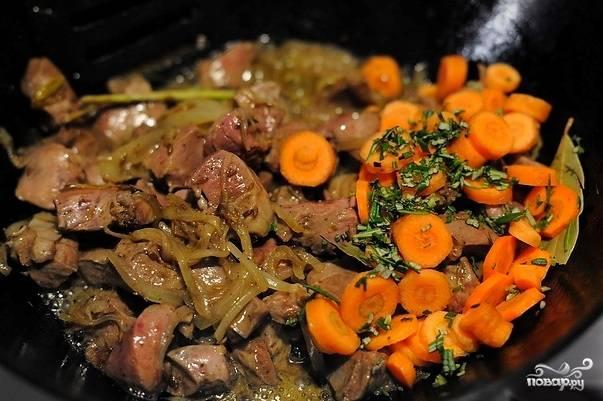 Помойте и почистите, если это необходимо, остальные овощи. Морковь нарежьте кружками, капусту нашинкуйте, картофель крупно нарубите. Отправьте всё в сковороду вместе с целыми дольками чеснока, солью, розмарином и перцем. Влейте немного воды.