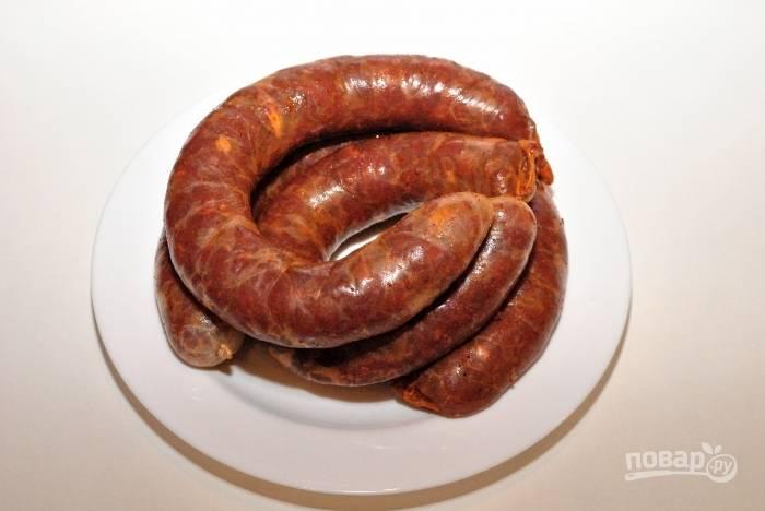 Наполняйте оболочку мясом очень плотно. Потом обвяжите колбасу ниткой и сделайте петельку для подвешивания.
