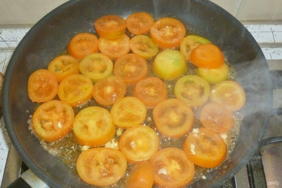 Если используете замороженное тесто, предварительно его разморозьте. Духовку разогрейте до 200°. Помидоры нарежьте кружочками. В сковороде растопите масло и всыпьте сахар. Помешивайте, пока сахар не превратится в светлую карамель. Выложите помидоры, пропустите через пресс чеснок. Протушите овощи на слабом огне 2-3 минуты.