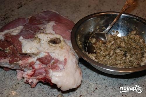 В миске смешиваем жир, измельченную головку чеснока, соль, розмарин и тимьян. Затем делаем ножом проколы в мясе, расширяем их немного пальцем и начиняем эти дырочки полученной смесью.