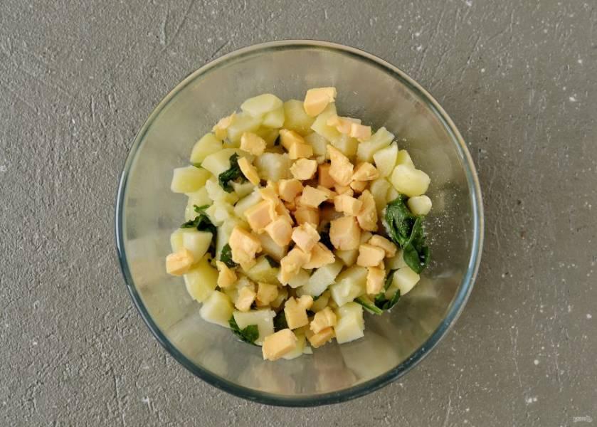 Веганский сыр нарежьте кубиками. Соедините в миске сыр, картошку и шпинат. Добавьте сухой чеснок, посолите по вкусу и перемешайте.