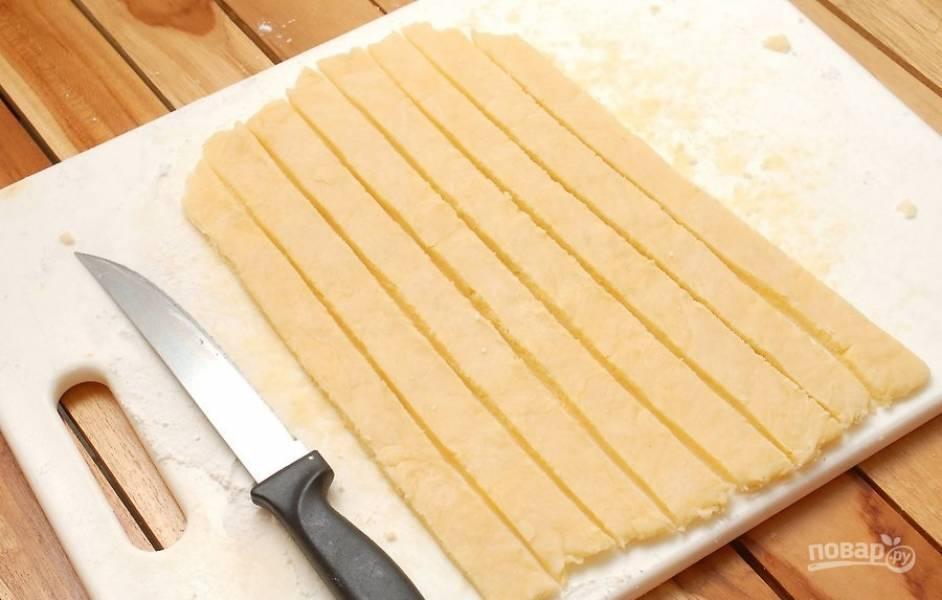 8.Оставшееся тесто достаньте из холодильника и раскатайте в пласт, затем нарежьте полосками.