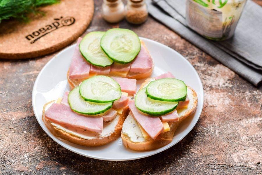 Свежий огурец нарежьте кружочками и выложите поверх ветчины. Подавайте бутерброды с ветчиной и огурцом к столу.
