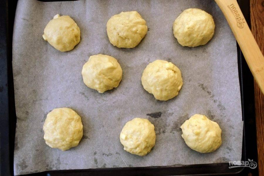 Тесто остается немного липким, поэтому руки смажьте растительным маслом. Разделите тесто на 16 частей, сформируйте булочки. Выкладывайте заготовки на противень с пергаментом для выпечки на расстоянии 2-3 см друг от друга. Оставьте в теплом месте на 40 минут для подхода.