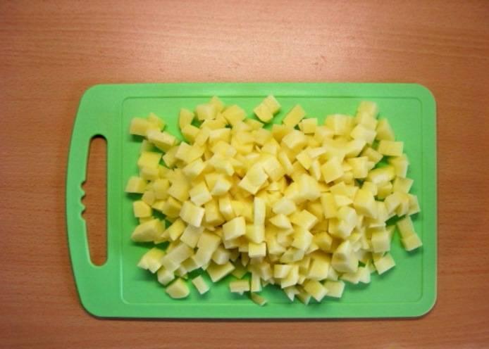 Картофель порежьте кубиками и добавьте в суп, когда перловка будет почти готова.