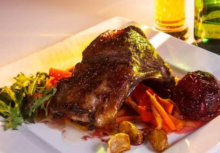 Когда мясо будет готово, выкладываем на порционную тарелочку горсть моркови с перцем, на нее кладем баранину, рядом выкладываем сливы и чеснок (его после обжарки следует выложить на бумажное полотенце). Поливаем блюдо соусом и подаем к столу. Приятного всем аппетита!