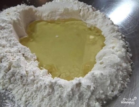 2.В муке делаем углубление и в него добавляем рафинированное масло. Туда же нужно отправить чистую воду. Предварительно ее лучше охладить.