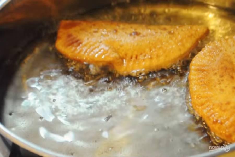 4. Хорошо разогрейте на сковороде подсолнечное масло и обжарьте в нем чебуреки до золотистого цвета. Аккуратно их переворачивайте, чтобы не порвать тесто.