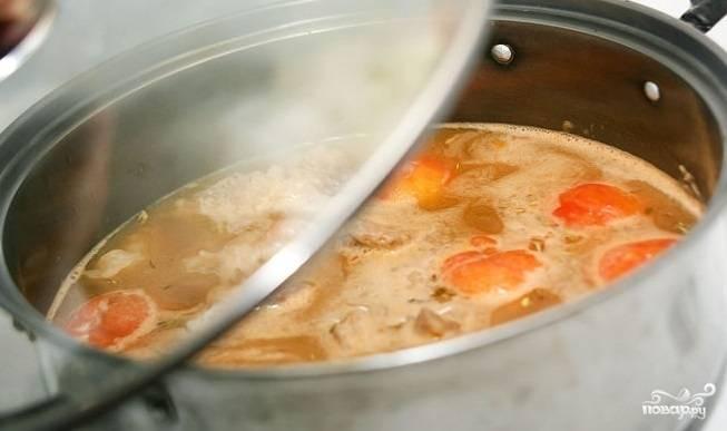 3. В кастрюле на масле обжарьте до мягкости лук, чеснок и морковь. Добавьте помидоры, специи, обжаренное мясо и залейте готовым говяжьим бульоном. Доведите до кипения, затем снизьте огонь до средне-медленного, накройте крышкой и тушите в течение часа.