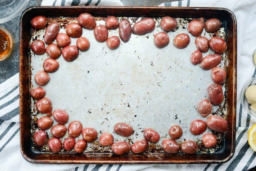 1. Для начала разрежьте картофель пополам. Разложите его на противень. Влейте немного масла. Добавьте соль и перец. Затем отправьте запекаться овощи на 10 минут в духовку при 200 градусах.