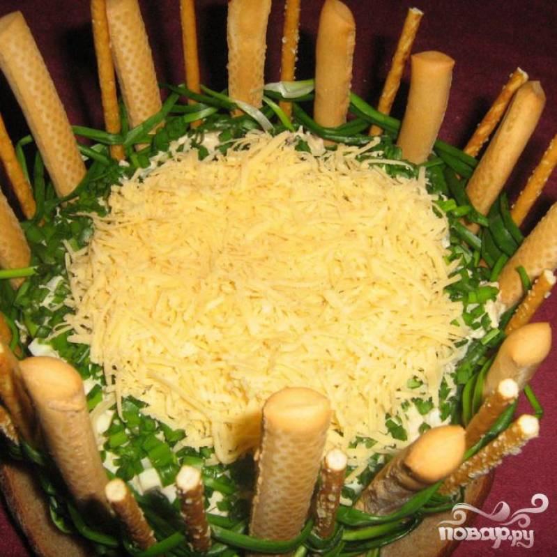 Красиво выкладываем тертый сыр по центру салата.