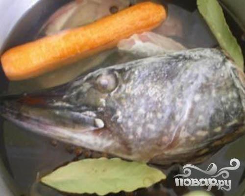 1.С очищенной рыбы возьмем хвост, плавники и голову. Все это складываем в кастрюлю и заливаем холодной водой. Поставим кастрюлю на плиту. А кастрюлю с рыбой добавляем очищенную луковицу, очищенную морковь, лавровый лист и черный перец горошком. Пускай бульон варится. Когда бульон сварился, вынимаем из кастрюли овощи, перекладываем на тарелку, и вилкой их разминаем. Затем обратно перекладываем их в кастрюлю. Теперь бульон надо процедить.
