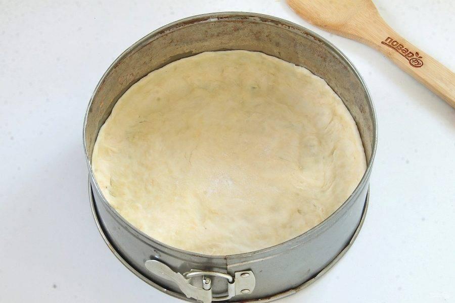 Разъемную форму смажьте маслом и выложите тесто, присыпанное мукой. Распределите его по всей окружности, формируя бортики высотой около 2 см.