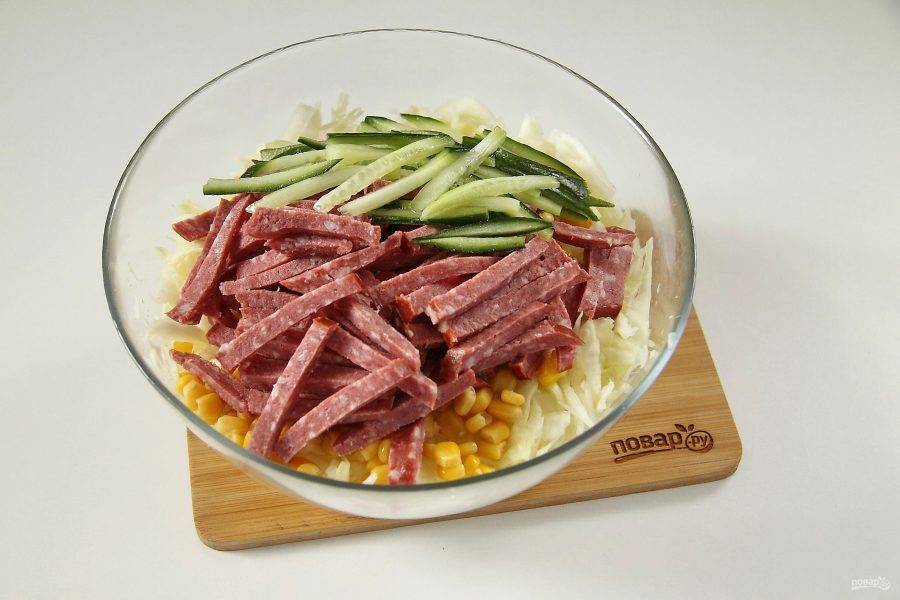Добавьте нарезанную соломкой колбасу и свежий огурец.