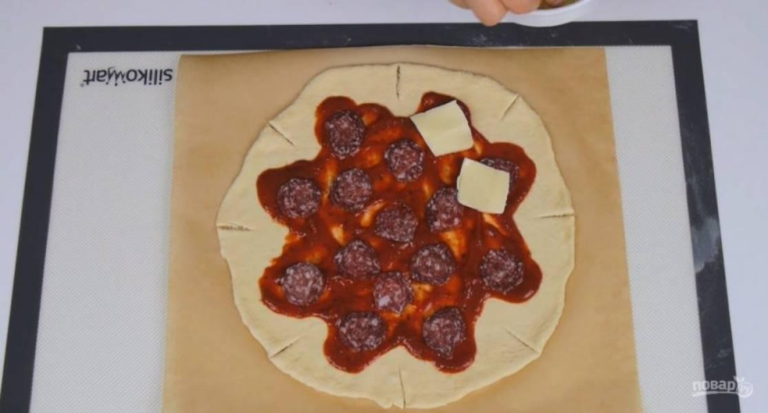2.  Перенесите тесто на бумагу для выпечки при помощи скалки. По краям основы сделайте 8 надрезов. Выложите в форме звезды томатный соус, затем — нарезанную салями и кусочки моцареллы.