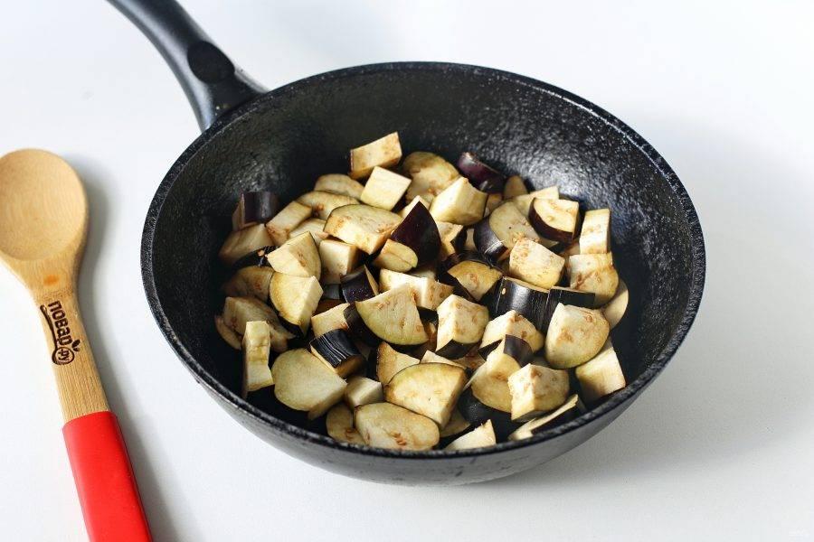 Баклажаны нарежьте небольшими кусочками и переложите в разогретую сковороду с маслом. Добавьте соль по вкусу и обжарьте баклажаны до полуготовности периодически помешивая.