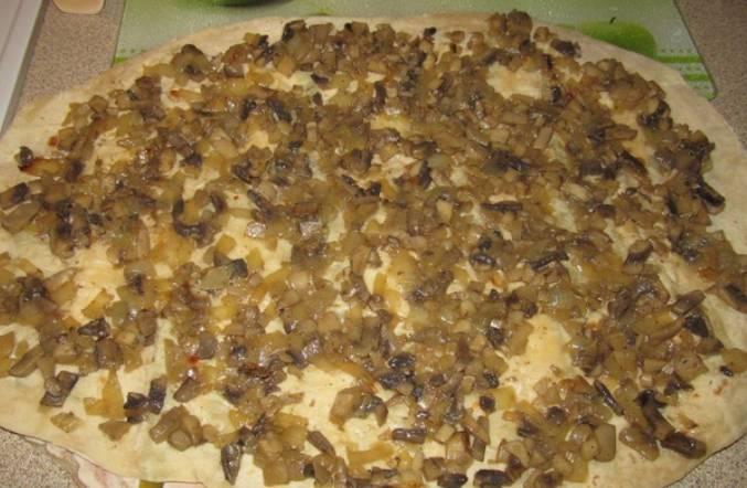 Измельчите лук и грибы, обжарьте их вместе на растительном масле до готовности. Затем выложите поверх лаваша.