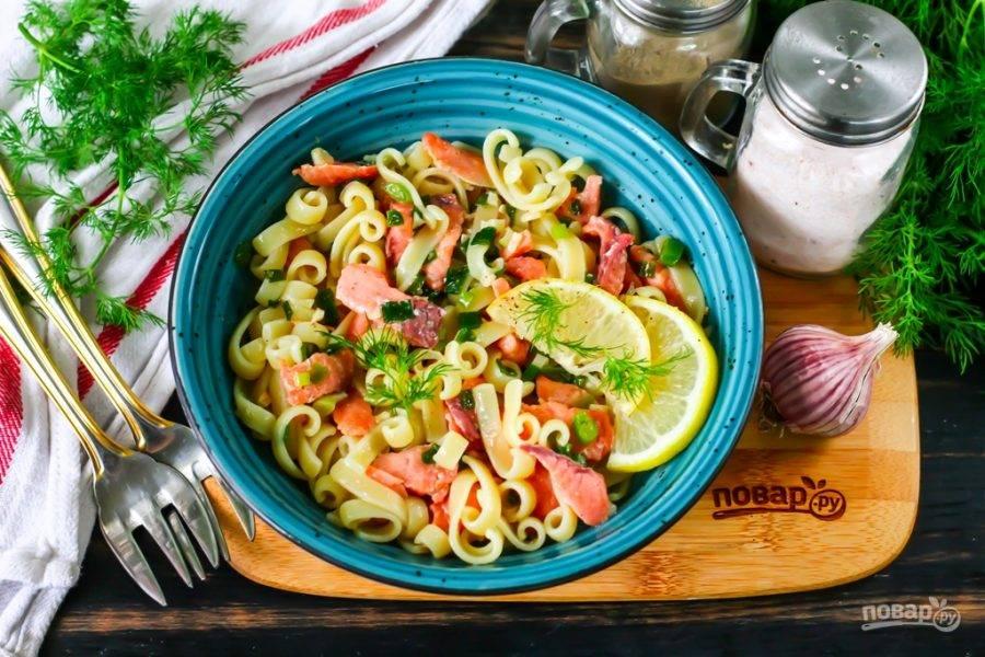 Выложите пасту с лососем на тарелки и подайте с ломтиками лимона, свежей зеленью. Приятного аппетита!