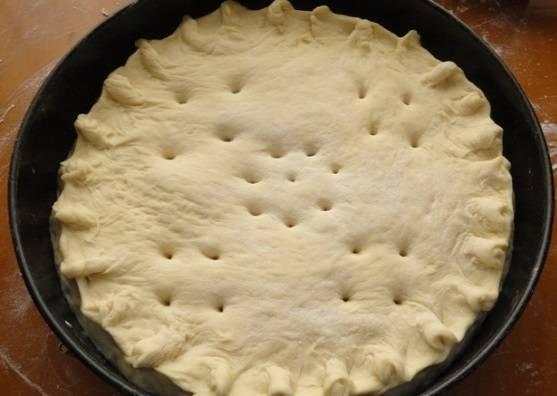6. Вторым кусочком теста накрыть начинку и тщательно защипить края, чтобы пирог не раскрылся в процессе выпечки. Также можно сделать небольшие отверстия для выхода пара. На данном этапе приготовления пирог нужно оставить на 10-15 минут, а за это время как раз разогреть духовку.