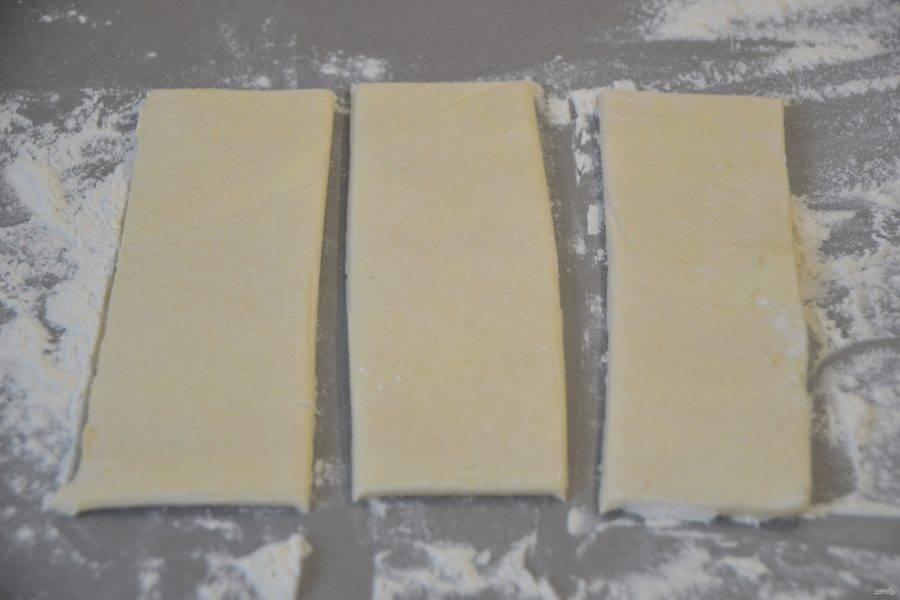Припылите рабочую поверхность стола мукой, разделите пластинку теста на полоски.