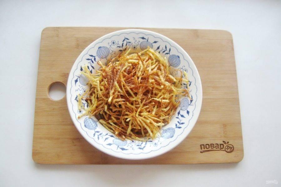 Подсолнечное масло налейте в кастрюлю с толстым дном или такую же сковороду. Хорошо нагрейте масло. Небольшими порциями отправляйте картофель в кипящее масло. Сразу будет очень сильное кипение, но через несколько минут пена спадет и дальше картошка будет равномерно обжариваться в масле. На каждую порцию уйдет примерно 6-7 минут на огне чуть меньше среднего. Готовую соломку выложите на бумажное полотенце для удаления лишнего жира.