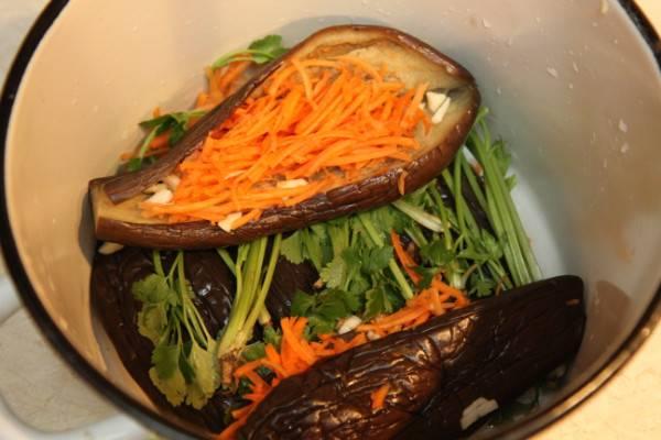 4. Аккуратно разрежьте синенькие (продольно), довольно плотно наполните их тертой морковью с чесноком. На дно подготовленной емкости отправьте немного зелени, затем выложите баклажаны. Переслаивайте 2-3 синеньких зеленью.