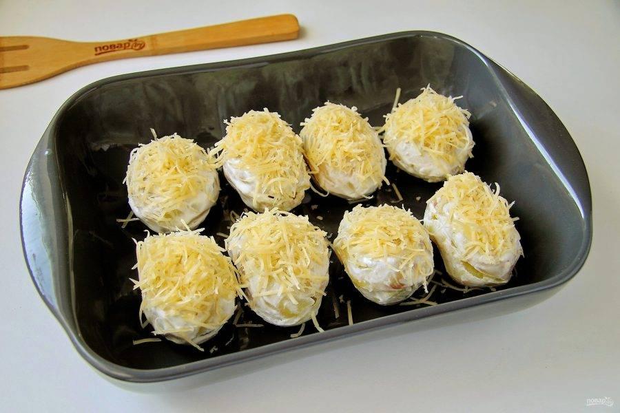 Обмажьте картофель сметаной и переложите в форму для запекания. Сверху посыпьте оставшимся сыром. Налейте на дно примерно половину стакана воды и накройте форму плотно фольгой. Запекайте при температуре 200 градусов около 20 минут. После чего снимите фольгу и дайте сыру подрумяниться.