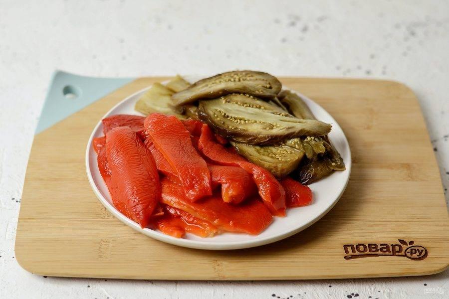 Остудите запеченные овощи. Болгарский перец очистите от кожицы, хвостика и семян. Нарежьте прямоугольными полосами. Баклажан тоже очистите от кожицы, затем нарежьте вдоль на ломтики.