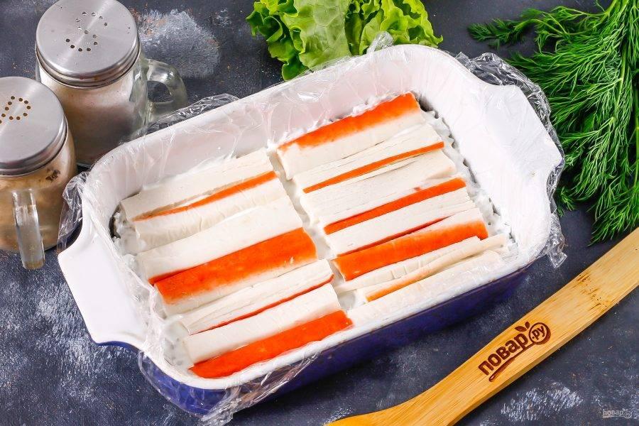 Рис смажьте сливочным сыром. Нарежьте крабовые палочки лентами и выложите на слой сыра.