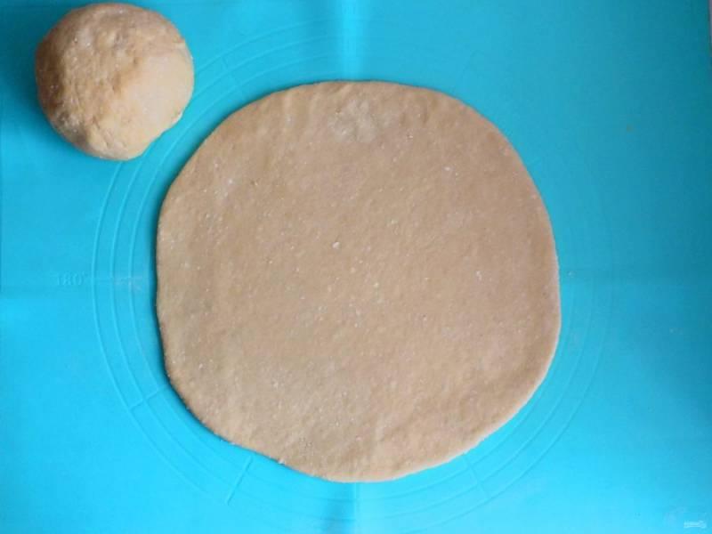 Отлежавшееся тесто разделите на две части. Одну из частей сделайте чуть меньше, примерно на 50 грамм. Возьмите часть побольше и раскатайте в пласт. Диаметр ориентировочно 28 см.