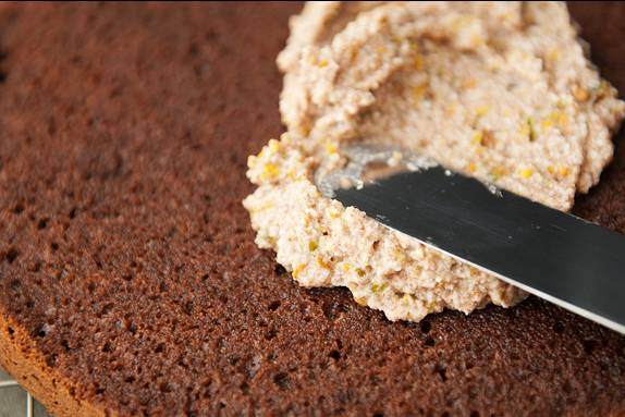 13. Полученной начинкой нужно смазать каждый корж, тогда бисквитный торт с пропиткой в домашних условиях будет еще более сочным и нежным.