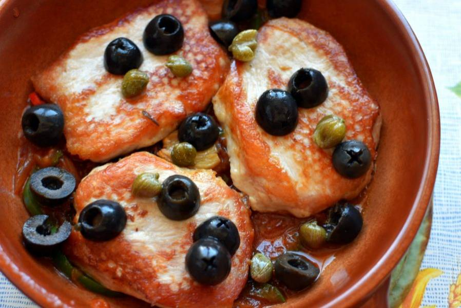 В керамическую форму вылейте часть овощного соуса, уложите сверху кусочки свинины. На свинину уложите маслины, разрезанные пополам, и каперсы.
