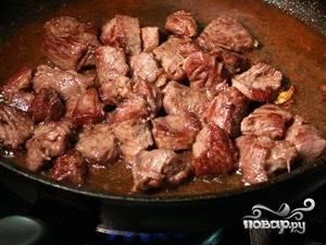 Мясо говядины также моем и режем на кусочки. Обжариваем на сковороде 15 минут до румяной корочки и перекладываем в ту же высокую сковороду к мясу свинины.