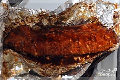 Запекайте ребра в духовке 2 часа при 180 градусах. Затем раскройте фольгу, смажьте соусом для барбекю и выпекайте еще 15 минут, снова закрыв фольгу.