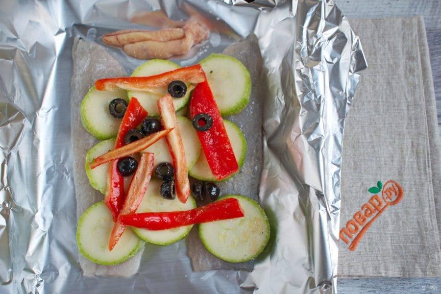 Рыбное филе выложите на фольгу, сверху - нарезанные овощи, маслины. Закройте тщательно фольгой, чтобы при запекании  все соки остались внутри.